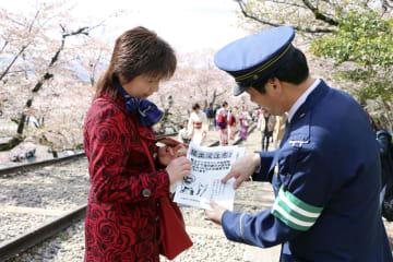 サルによる被害への注意を呼び掛けるチラシを配る警察官=京都市