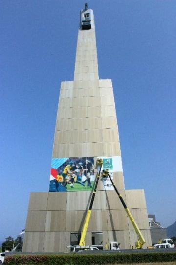 ビーコンプラザのグローバルタワーに設置されるラグビーW杯の巨大パネル=19日、別府市