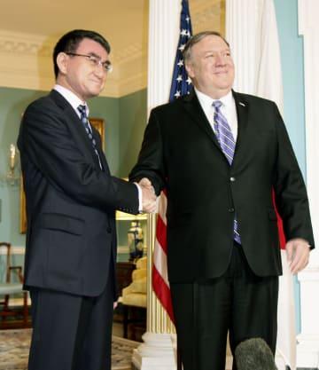 19日、米ワシントンの国務省でポンペオ国務長官(右)と握手する河野外相(共同)
