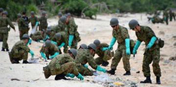 廃油ボールを回収する自衛隊の隊員=19日、宮古島市・新城海岸