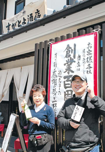 再建した店舗の前で記念酒を手にする文子さんと英樹さん