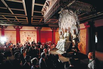 法隆寺金堂の釈迦三尊像の精巧な複製を鑑賞する来場者