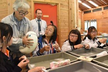 西都原古代生活体験館の指導員の手ほどきで、勾玉作りを体験する台湾の中高生