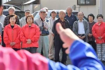 真剣な表情で町長選候補者の演説を聞く支持者ら=20日午前8時半ごろ、御船町(池田祐介)
