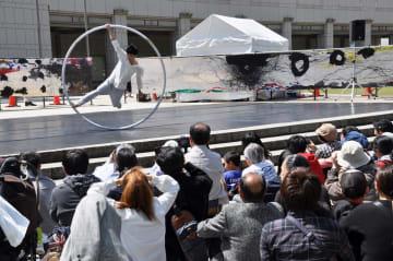 「シルホイール」と呼ばれる輪を使ってアクロバティックな動きをする「シルクブラン」のパフォーマー=横浜市西区のグランモール公園・美術の広場