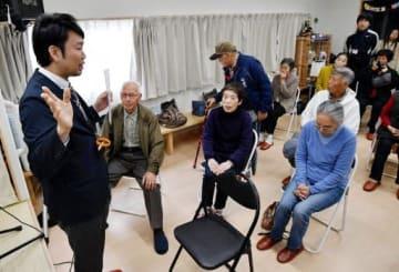 仮設住宅の入居者たちに避難情報について説明する木下さん=左端(広島県坂町)