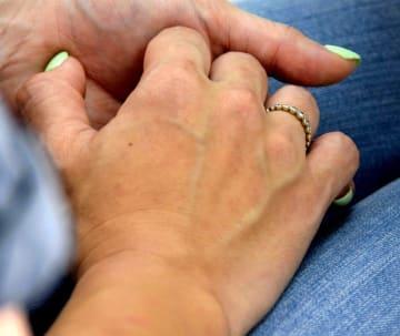 父親から託された被害者の指輪を付け、残された家族のつらい心情や思いを伝える友人の女性=19日、沖縄タイムス中部支社