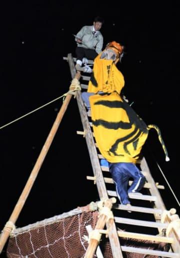高さ約16メートルのはしごで虎舞を練習する住民ら