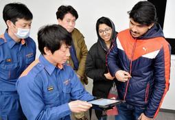 翻訳アプリを試す防災訓練の参加者と消防職員=市消防本部