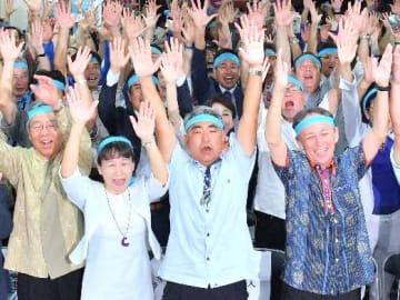 「当選確実」となり、支持者とバンザイ三唱する屋良朝博氏(中央)=21日午後8時すぎ、沖縄市安慶田の選挙事務所