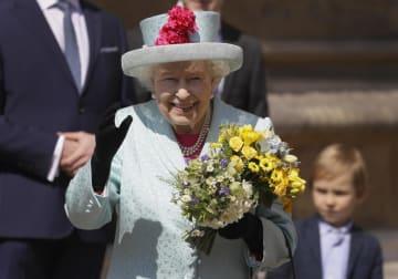 花束を手に笑顔を見せるエリザベス女王=21日、ウィンザー(ゲッティ=共同)