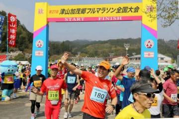 一斉にコースへと駆けだしていくフルマラソンの選手たち=津山市加茂町スポーツセンター総合グラウンド
