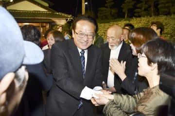 再選を確実にし、支援者と握手する渕上隆信氏=4月21日午後10時15分ごろ、福井県敦賀市野神の選挙事務所