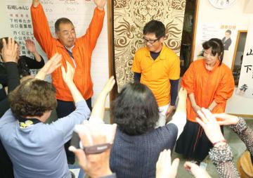 新富町議選でトップ当選を果たし、支持者から祝福を受ける石崎俊二さん(中央)=21日午後8時23分、新富町三納代の選挙事務所