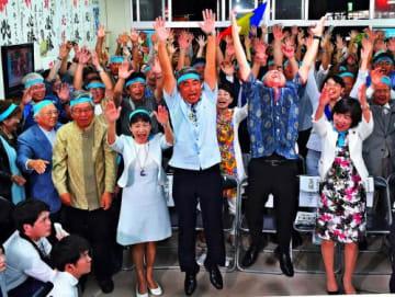 「当確」が出た後、支持者と共にバンザイ三唱する屋良朝博氏(前列右から3人目)と玉城デニー知事(同2人目)=21日午後8時14分、沖縄市安慶田の選挙事務所(下地広也撮影)