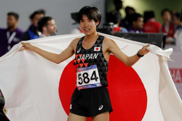 陸上のアジア選手権第1日、日の丸を背に笑顔を見せる3000m障害の塩尻和也=21日、ドーハ(AP=共同)