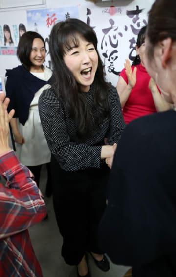 宮崎市議選で当選確実となり、支持者たちと喜ぶ冨永千香さん(中央)=22日午前0時18分、宮崎市橘通西2丁目の選挙事務所