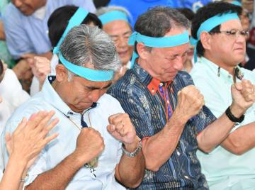 テレビで当確の速報が出た瞬間、両手を握りしめて喜ぶ屋良朝博氏(左)と玉城デニー知事=21日午後8時、沖縄市安慶田の選挙事務所(田嶋正雄撮影)