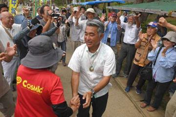 米軍キャンプ・シュワブのゲート前で、新基地建設に反対する市民と握手する屋良朝博さん(中央)=22日午前、名護市辺野古
