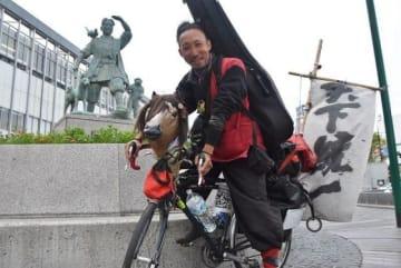 愛馬と呼ぶ自転車に乗り、県内を旅する信長さん=JR岡山駅前