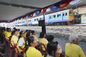 タイ東部アランヤプラテートからカンボジア北西部ポイペトに向かう一番列車を見守る住民ら=22日(共同)