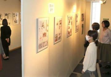 天皇皇后両陛下の写真が掲載された紙面に見入る入場者