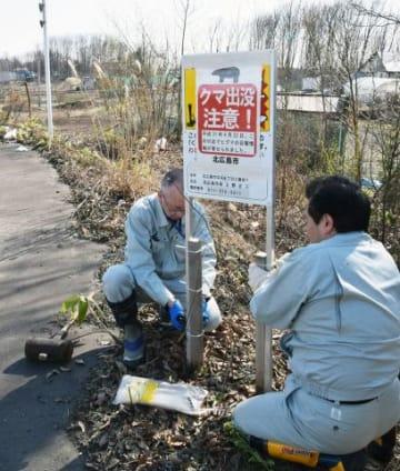 目撃のあった三井アウトレットパーク札幌北広島付近にクマ出没を知らせる看板を設置する北広島市職員=22日午後2時45分