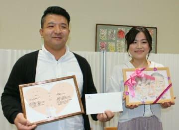 記念品を受け取り、笑顔の塩月大志さん(左)と春佳さん夫婦=22日、大分市