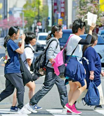 手提げ袋で日差しをよけたり、アイスを食べたりしながら歩く若者たち=22日午後1時32分、岐阜市神田町