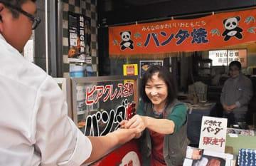 10連休のスタートが迫る中、健軍商店街の和菓子店で買い物客に釣り銭を渡す店員=20日、熊本市東区