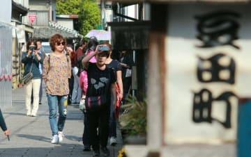 日差しを手で遮りながら散策する観光客も=22日午後、日田市豆田町