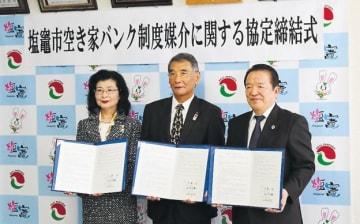 署名した協定書を手にする(左から)小林本部長、佐藤市長、佐々木会長