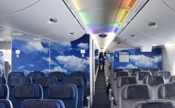 壁に青空が描かれ、一部の照明が青や虹色に変化する機内=23日、成田空港