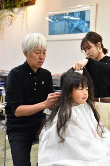 医療用かつらへ寄付するため重留代表(左)から長い髪をカットしてもらう耕伽君