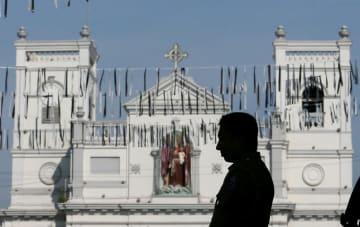 23日、スリランカの最大都市コロンボで、爆破テロのあった聖アンソニー教会の前で、犠牲者を悼み黙とうする治安部隊員(ロイター=共同)