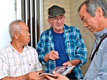 約50年前にお世話になった「嘉手苅さん」の次男・晃さん(右)らとの再会を喜ぶ元米空軍兵のグローバー・レデンさん(中央)=嘉手納町屋良