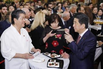 日本政府主催のレセプションで、日本食をPRする安倍首相(右)=23日、ローマ(共同)