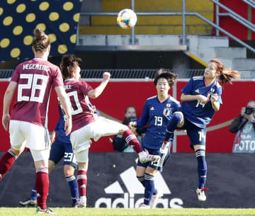 女子国際親善試合、日本―ドイツの前半、空中で競り合う長谷川(右端)=パーダーボルン(共同)
