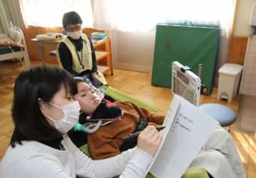 早島支援学校の教員と電子端末やノートでコミュニケーションを取る新井君(中央)