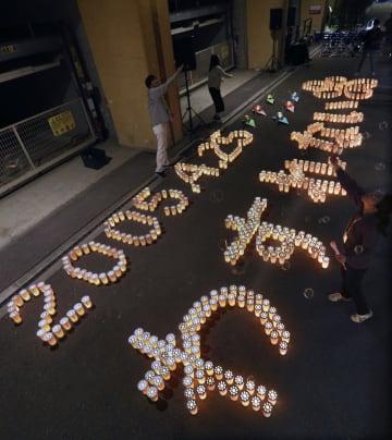 尼崎JR脱線事故の犠牲者の鎮魂と風化防止を願い、現場マンション前に浮かび上がった「2005.4・25 わすれない」の文字=24日夜、兵庫県尼崎市(代表撮影)