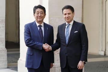 首相府に到着し、イタリアのコンテ首相(右)と握手する安倍首相=24日、ローマ(共同)