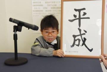 小渕さんになりきり「平成」の書を掲げる来館者