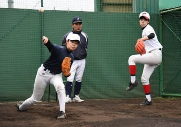 投球練習に励む学芸館高の女子硬式野球部員。奥は山崎監督