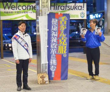 舌がんを克服した経験を語り、支持を訴えた平塚市議選の新人・渡部亮氏(左)=17日午後6時半、JR平塚駅前