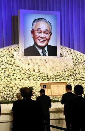 多田氏の遺影を掲げた祭壇へ献花に向かう参列者
