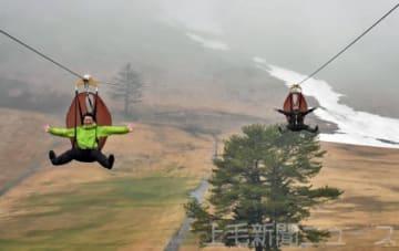 ジップラインで滑空を体験する関係者