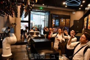 ロボットがコーヒーを作る店を視察する一行
