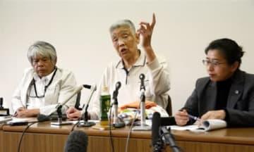 救済法成立を受けて開いた記者会見で、「侮辱されているとしか思えない」と憤る渡辺数美さん(中央)=24日、熊本市中央区