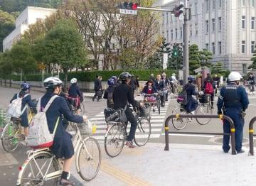 ヘルメットを着け、自転車で通勤や通学する人たち=2015年12月、松山市