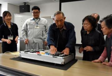 反射測定器で自分の動作年齢をチェックする参加者